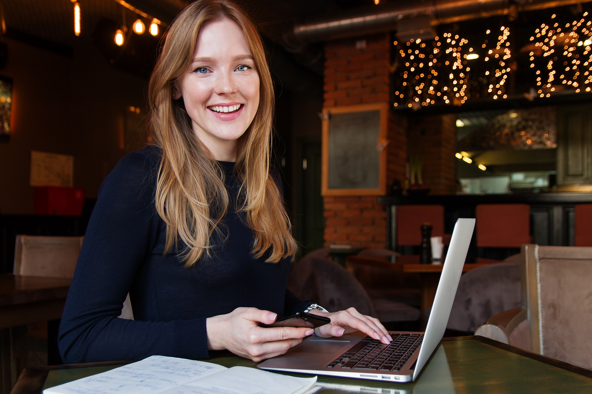 A woman with a laptop, smiling